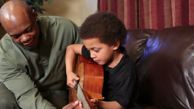 Father teaching son to play guitar video