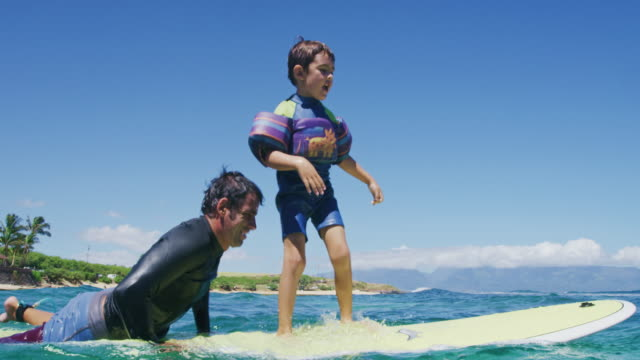 Father teaching son to surf tandem surfing video