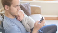 Father texting with newborn son asleep on his chest video