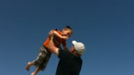Father throwing son in air, slow motion video