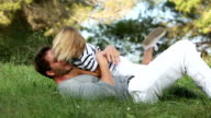 father tickling his son playing in the grass video
