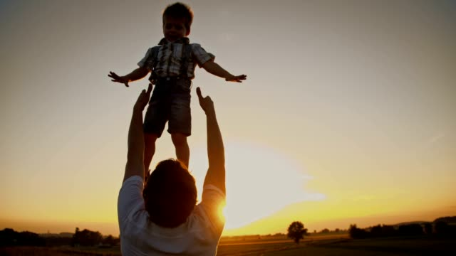 SLO MO Father tossing his son at sunset video