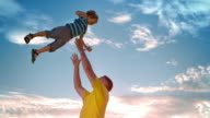 SLO MO Father tossing son into air in sunshine video