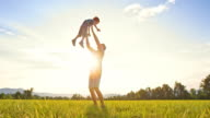 SLO MO DS Father tossing son into air in sunshine video