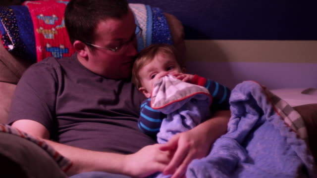 A father turns out the lights after reading his little boy a book before bed video