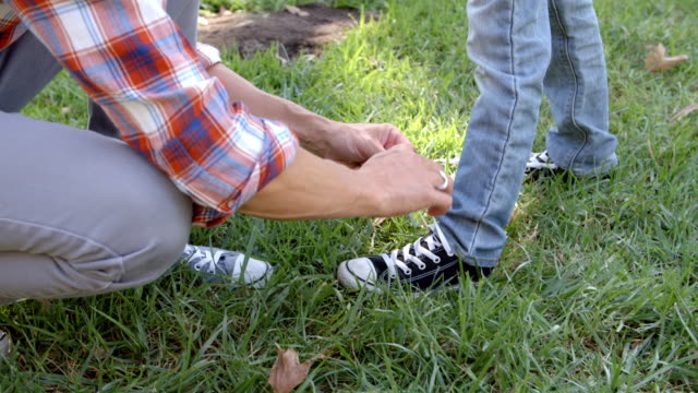 Father tying his son's shoelace in a park, low section video