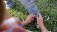 Father tying his son's shoelace in a park video