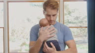 Father walking and bouncing newborn son in living room video
