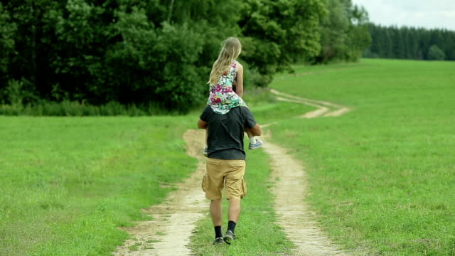 father walking road daughter sitting on his neck video