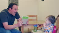 A father with a tablet taking photos of his baby boy eating in a high chair booster seat video