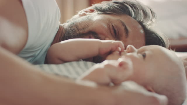 Father with child lying in bed video