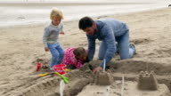 Father with children building sandcastle on beach together video