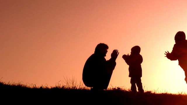 Father with children play ladushki. video