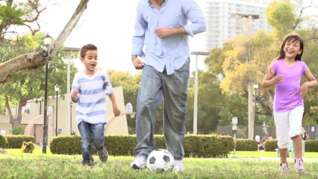 Father With Children Playing Soccer In Park Together video