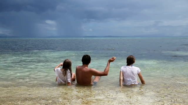Father with daughters throw pebbles into the sea video