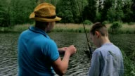 Father with little son the fishing on the bench of the lake video