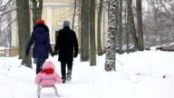 Father with mother pulling baby daughter on sled through snowy tree alley video