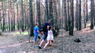 Father with son and daughter walking in forest video
