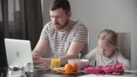 Father working and checking kid's homework video