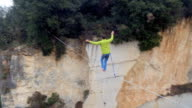 AERIAL: Fearless active guy slacklining on highline over deep abandoned quarry video