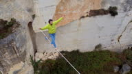 AERIAL: Fearless guy balancing on bouncy slackline tensioned over deep quarry video