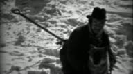 1936: Fedora hat man caring for dog in winter snowscape scene. video
