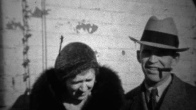 1933: Fedora hat man smoking cigar with loyal wife in black fur coat. video