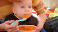 feeding baby with a spoon while watching cartoon video