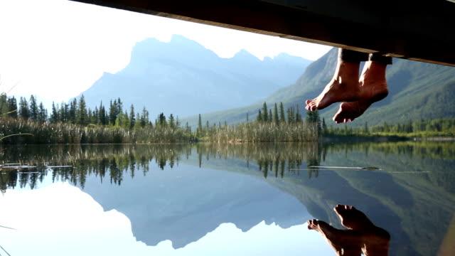 Feet dangle from mountain boardwalk at sunrise, above lake video