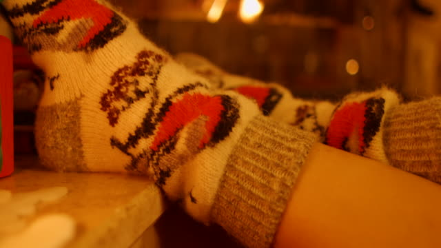 Feet girl with warm socks by the fireplace video