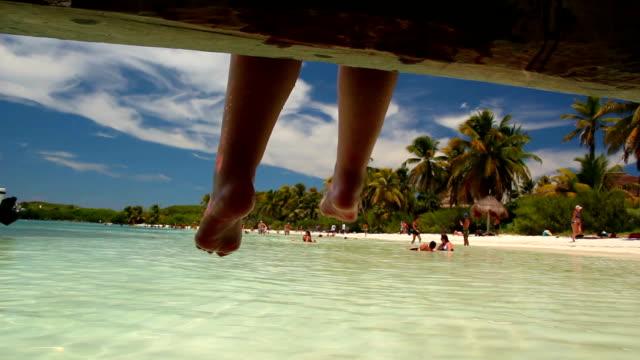 Feet hanging off pier on a beautiful desert island video