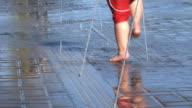 Feet of young boy walking in fountain video