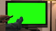 Feet up, watching chromakey TV and changing channel. video