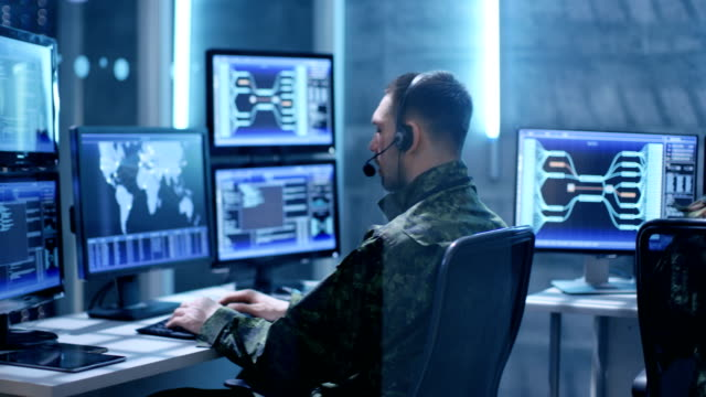Female  and Male Military Technical Support Professional Giving Instructions into Headsets. They're in System Control Room with Many Working Screens. video