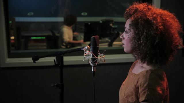 Female and  technician in recording studio video