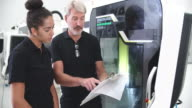 Female Apprentice Working With Engineer On CNC Machinery video