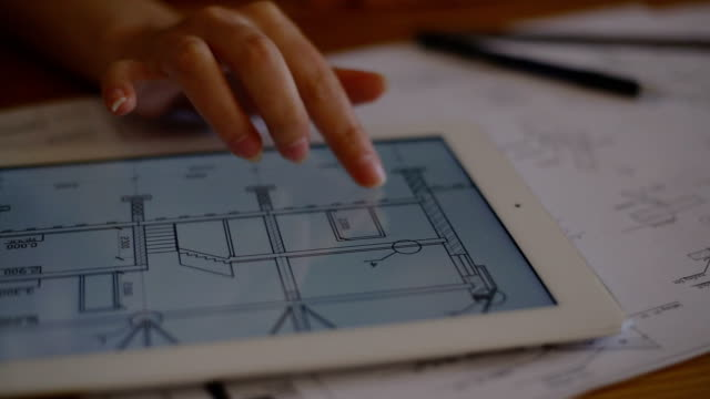 Female Architect Studying Plans In Office at desk with plans video