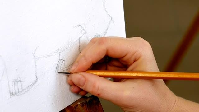Female artist draws a pencil sketch in art studio video