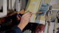 Female artist paints oil painting in the studio. video