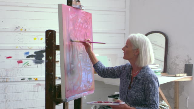 Female Artist Working On Painting In Studio Shot On R3D video