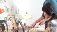 Female artist working with her teacher in the workshop. video