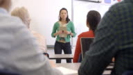 Female Asian teacher with tablet takes adult education class video