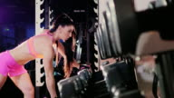 Female athlete doing exercise with a dumbbell in the gym. In the spotlight video