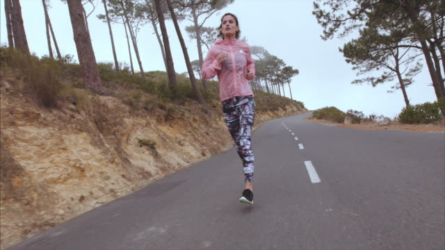 Female athlete running on country highway video