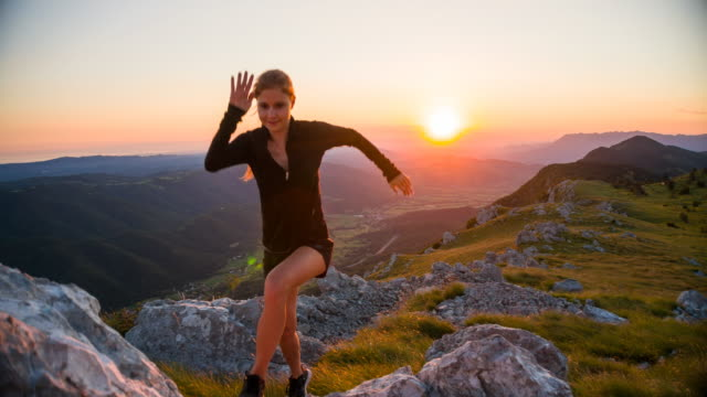 Female athlete running on rocky terrain in mountains at sunset video