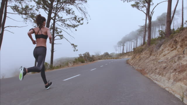 Female athlete sprinting on countryside highway video