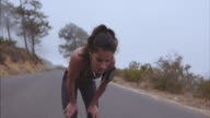 Female athlete taking breath from running video