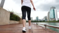 Female Athletic walking on sidewalk in City. closeup foot video