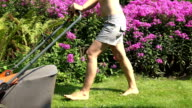 female barefoot cut meadow lawn mower in park with flower video