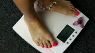 Female barefoot legs stepping on digital floor scales video